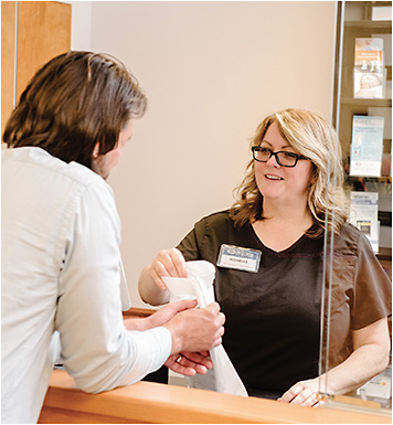 As a convenience to patients, The Dry Eye Center of Excellence offers dry eye disease treatment products at the front desk. Here, Michelle Rathmell, opthalmic assistant, helps a patient.