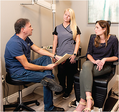 Peter J. Polack, MD, FACS, (left) and Carrie Davis, ophthalmic technician (center), discuss exam results and a treatment plan with a dry eye patient.