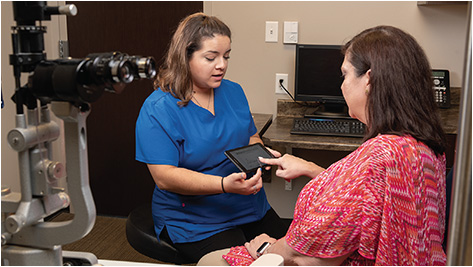 Medical Assistant Gabriela Mendoza, COA (left) helps a patient with Systeem Connect, an automated patient payment assistance program.