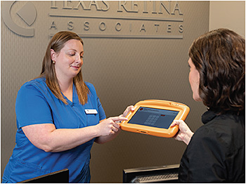 At the front desk, Receptionist Kerra Scrimshire demonstrates the Phreesia patient intake system to the patient.