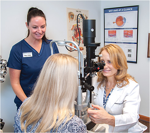 Cathleen McCabe, MD (right), examines a patient at the slit lamp while Lisa Olesen, COA, observes.